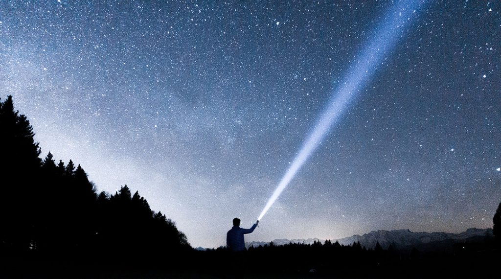 Man holding flashlight outdoors, with light beam against a starry night sky.