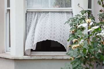 Breeze blowing lace curtains out an open windwo
