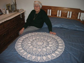 Frances sitting on bed next to prized crocheted doily