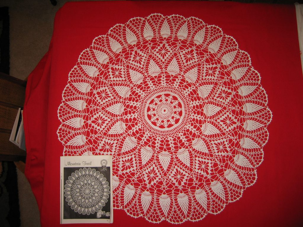 30-inch diameter crocheted doily on red background with pattern book