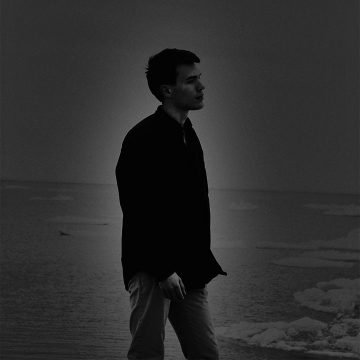 hazy, dreamy photo of a young man walking by the sea