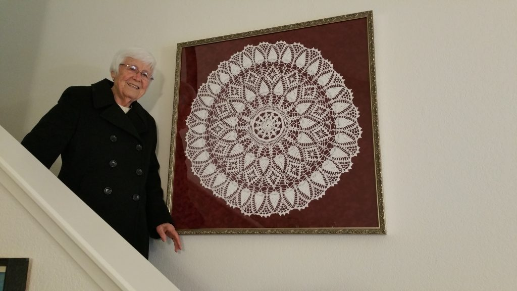 Frances with framed crocheted doily on stairway wall
