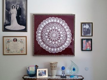 Large, framed crocheted doily, hung on wall with other family photos