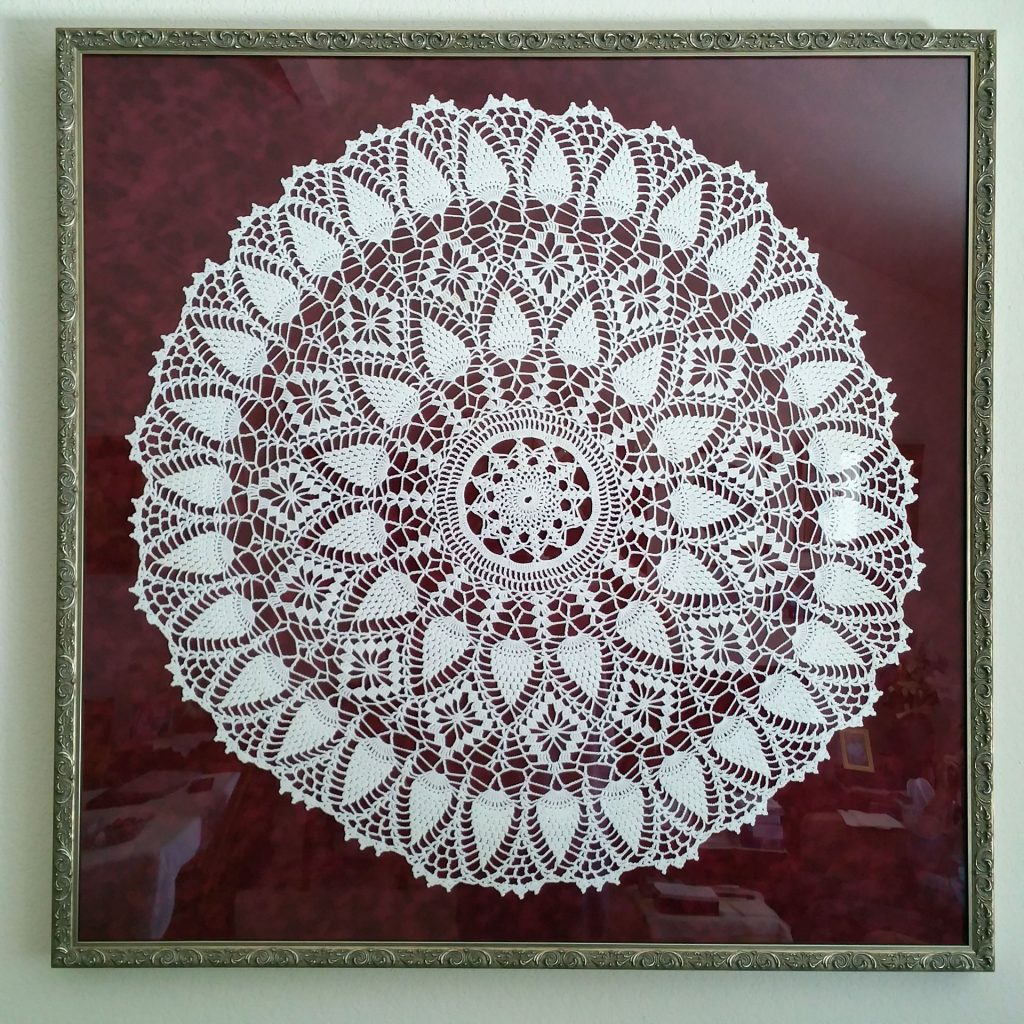 30-inch diameter white crocheted doily mounted on deep red velour, trimmed with an ornate scrollwork frame