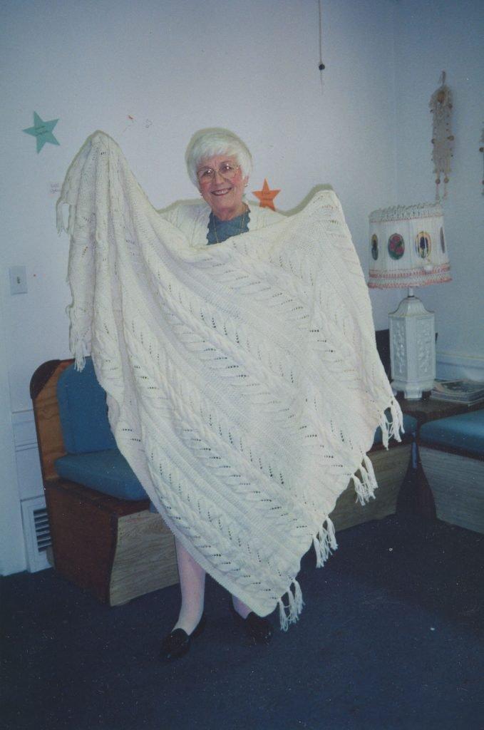Photo of Frances holding up large, white afghan blanket